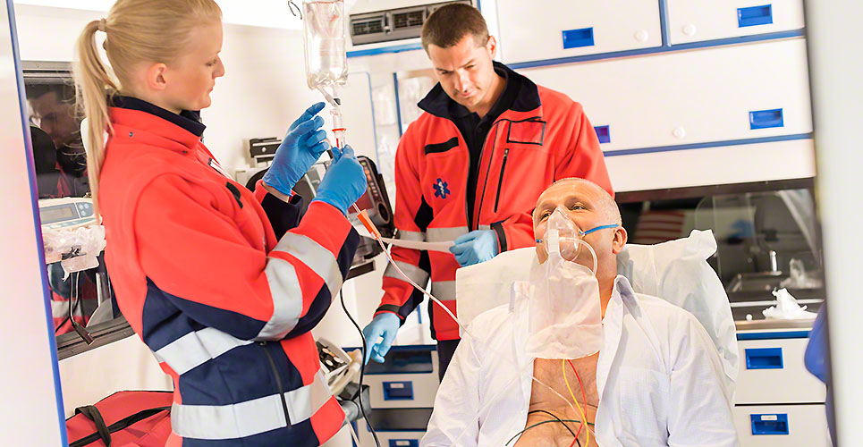 Paramedic putting oxygen mask on patient ambulance