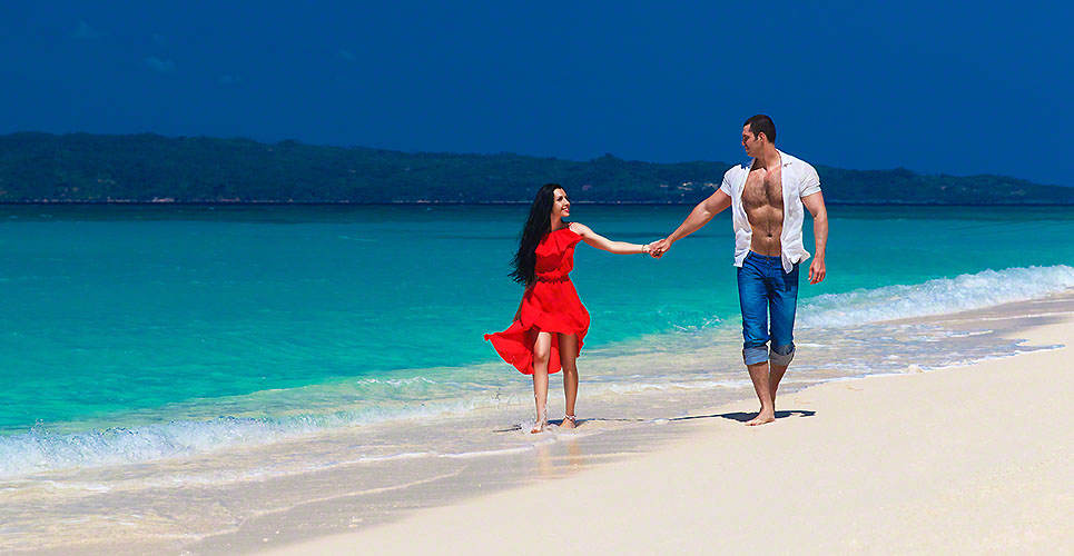 young loving couple walk through the tropical beach