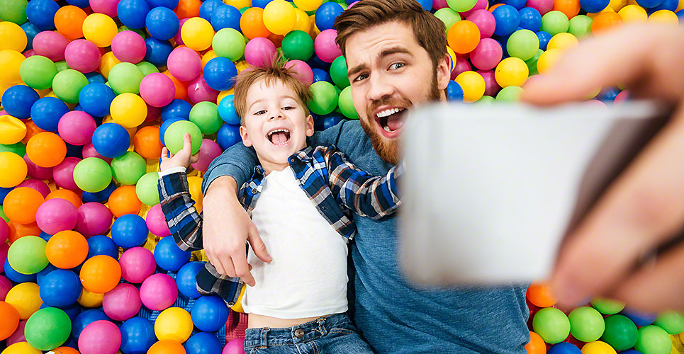 Son and dad taking selfie lying on colorful balls