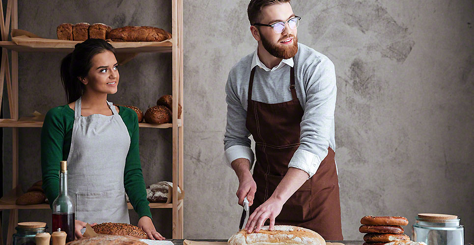 Cheerful loving couple bakers looking aside.