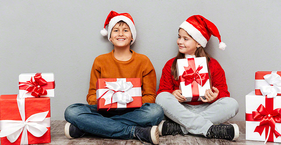 Two cheerful children in santa claus hats holding present boxes