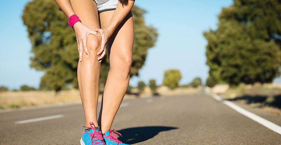 Legs of a female runner holding her knee