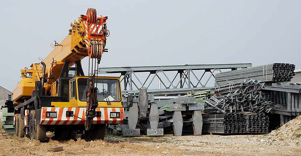 Front view of a telescopic crane truck  next to scaffolding and metal structures for the construction of a new building