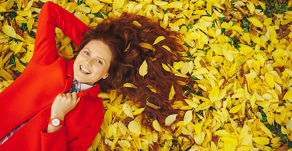 Young beautiful lady surrounded autumn leaves