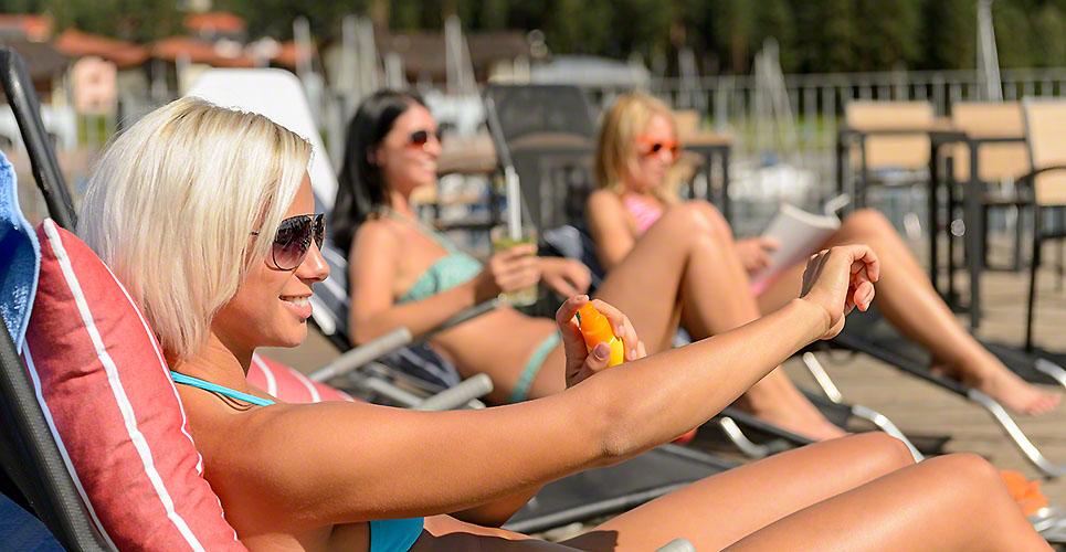 Young women lying on deckchair applying sunscreen